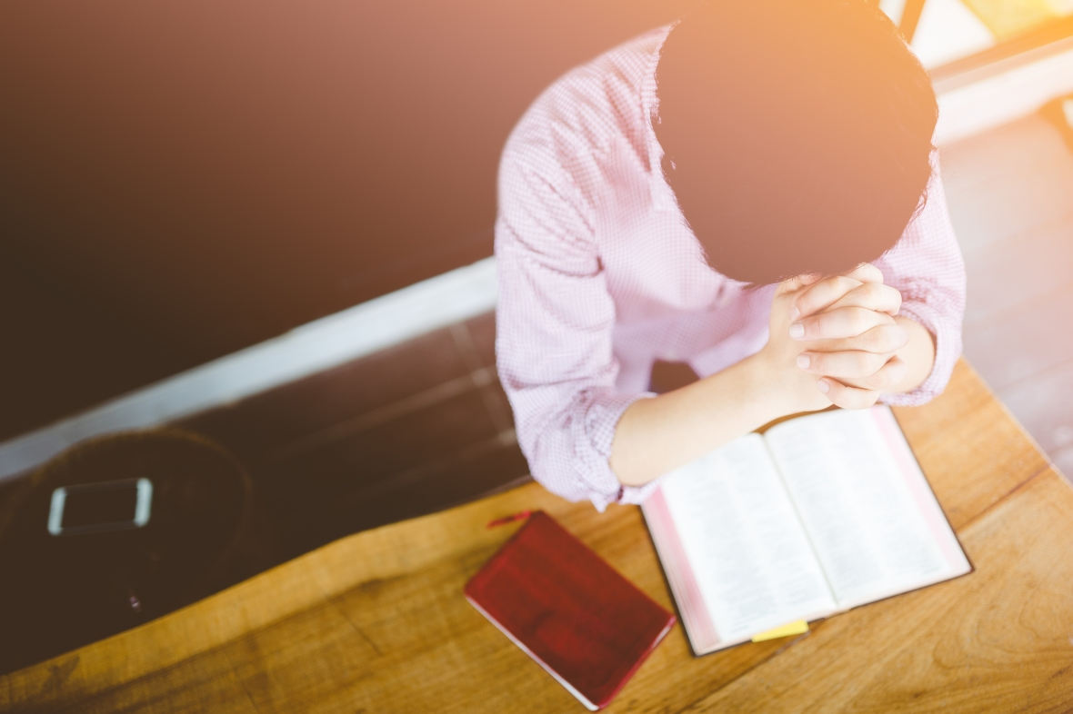 man praying on holy bible in the morning